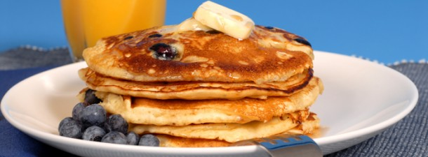 Blueberry pancakes with maple syrup and orange juice